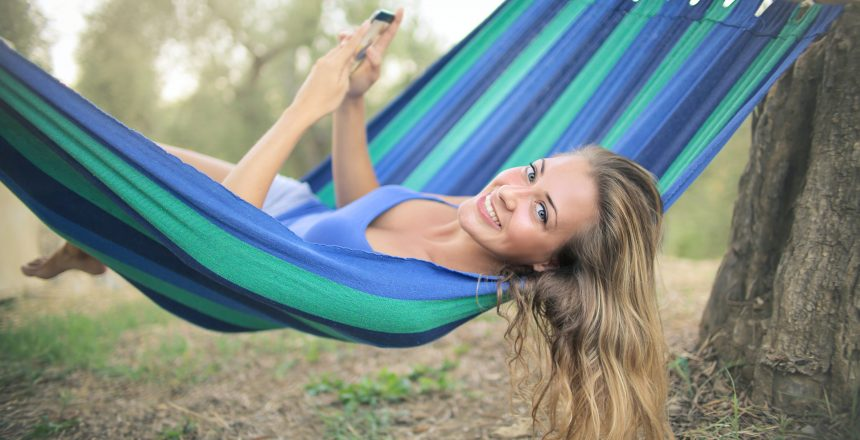 cheerful-young-woman-resting-in-colorful-hammock-3771818